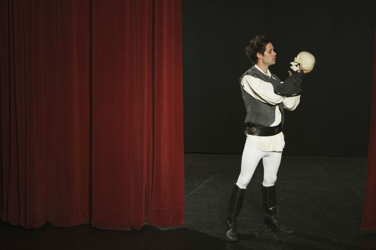 Actor holding skull on stage