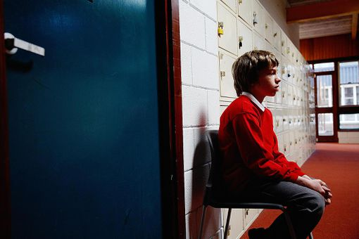 Schoolboy (11-13) sitting on chair in corridor, side view