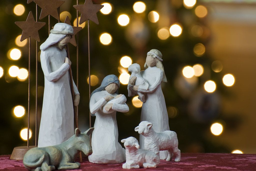 Nativity scene with Christmas lights in the background.