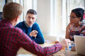 Three people talking at table