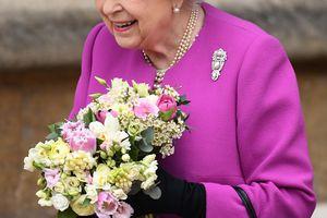 Queen Elizabeth II in purple holding a bouquet.