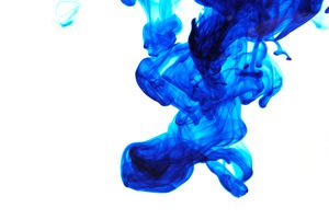 Blue dye in water against a white background demonstrating fluid dynamics