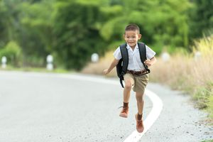 Young boy wearing a private school uniform skipping down the street.