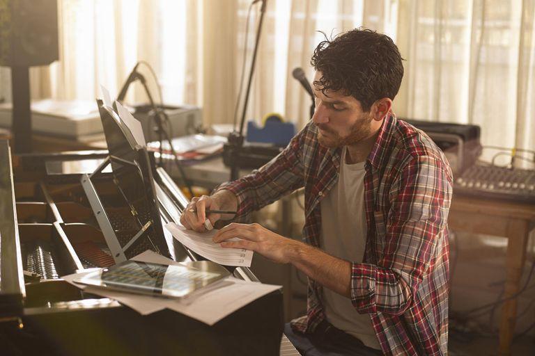 Man writing music at piano