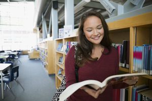 Smiling high school student reading book in library