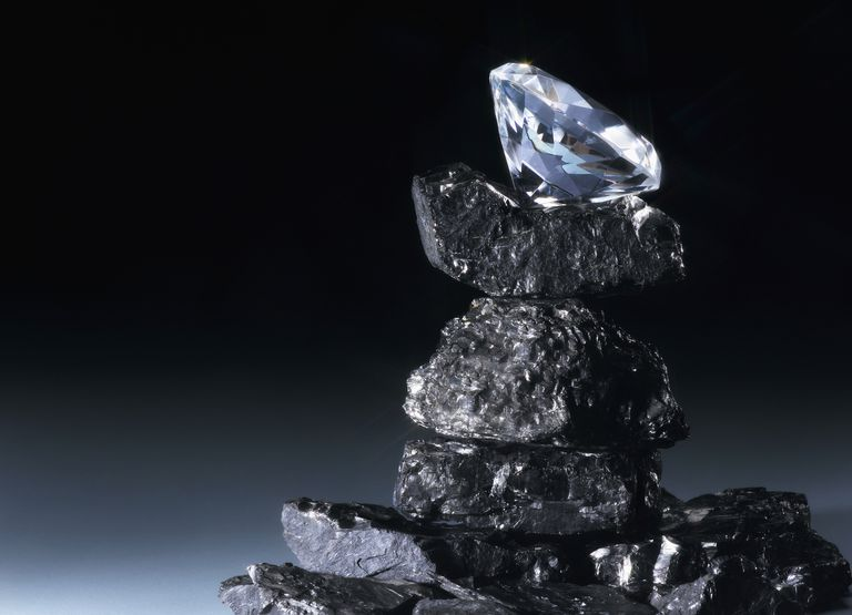 Diamond balanced on top of pile of coal.