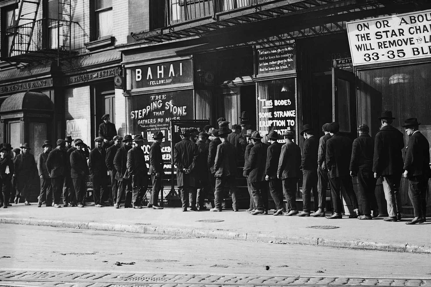 Unemployed men queuing for coffee and bread at a soup kitchen run by the Bahai Fellowship at 203 East 9th Street, New York, circa 1930