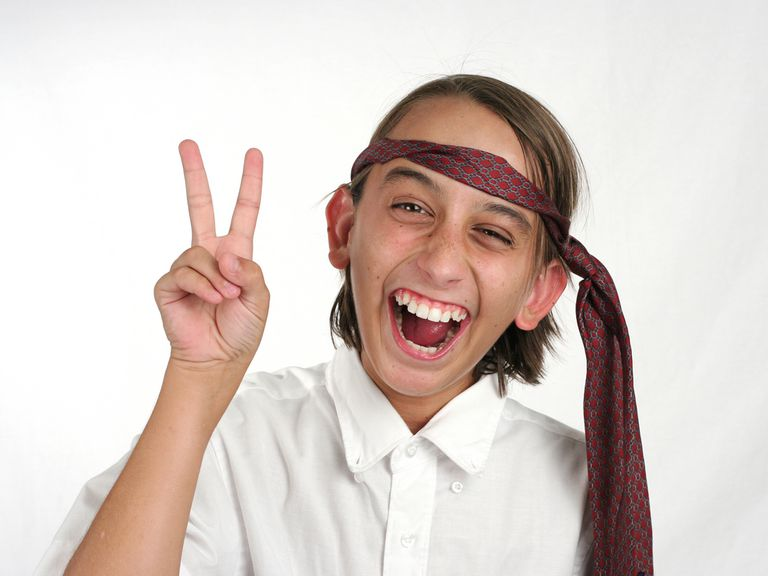 Child with tie on head, holding up peace sign.