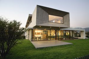 two story modern house with windows, piers, and oversized second story