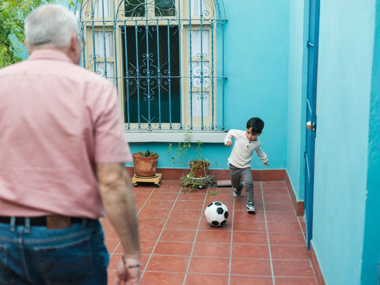 boy and grandfather playing with soccer ball