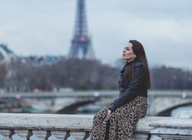 Woman with a bored expression sitting on a stone railing with the Eiffel Tower in the distance.