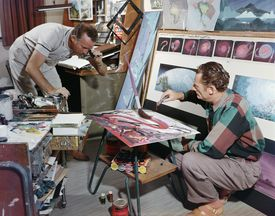 Walt Disney looks through a lens at an oversized paintbrush while a man drips paint from a tube