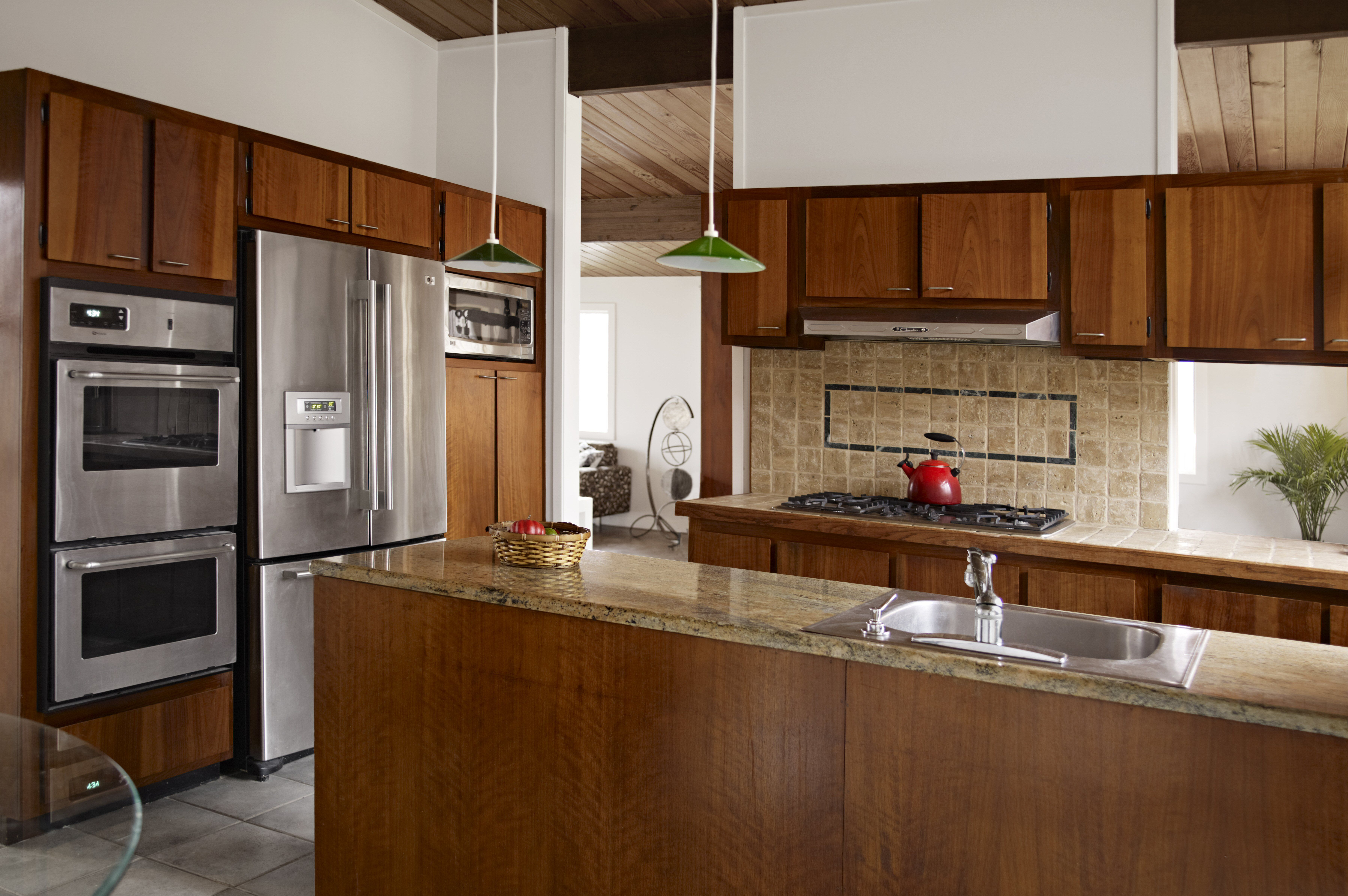 Feng shui kitchen with sink in island, range opposite wall, and refrigerator at the end.