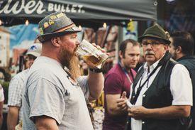 German men drinking beer at an outdoor event.