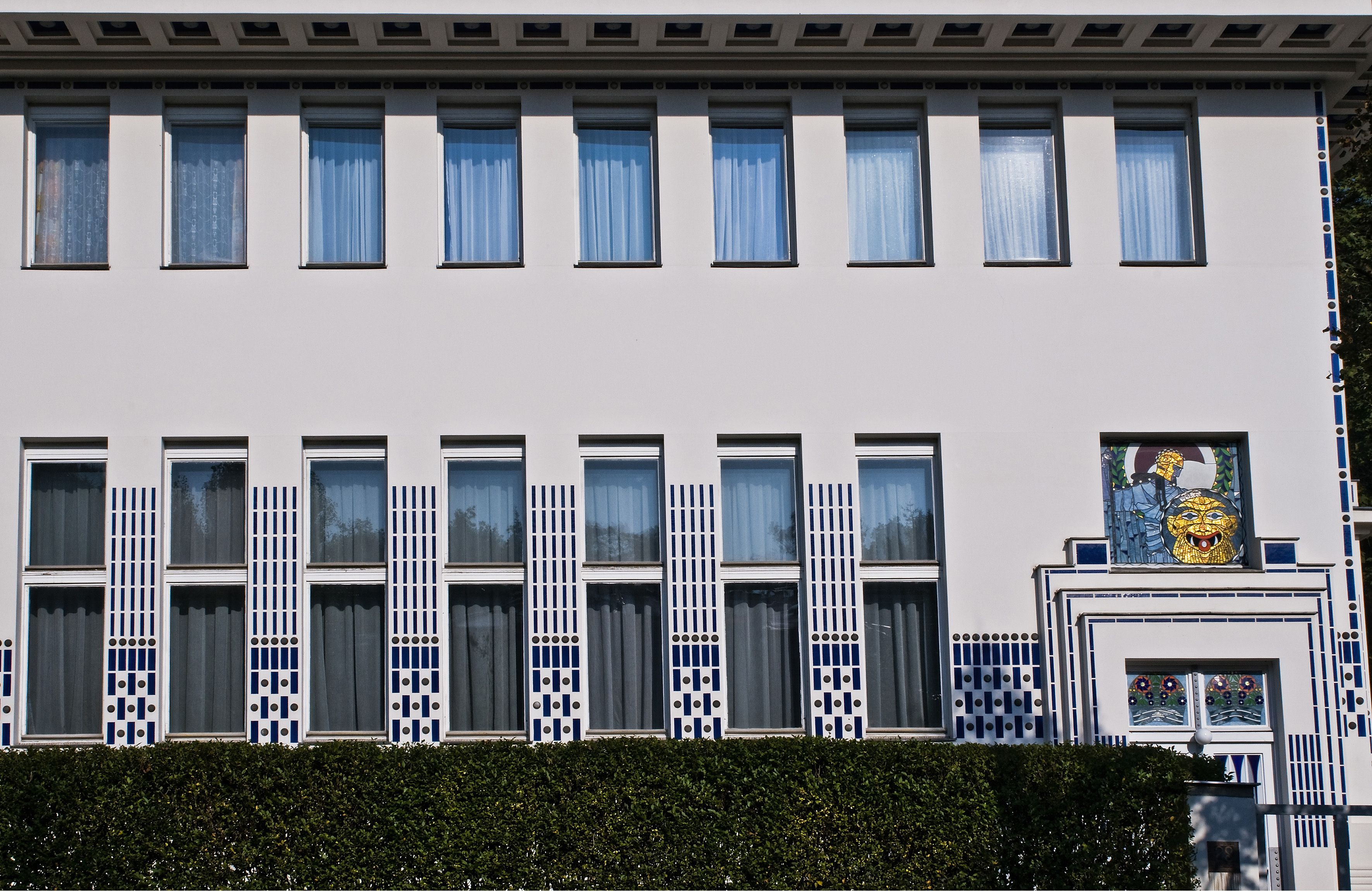 facade with symmetrical, elongated windows, overhanging eave, first floor ornamentation between the windows
