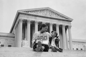 Nettie Hunt and her daughter, Nickie, sit on the steps of the U.S. Supreme Court. Nettie holding a newspaper reading