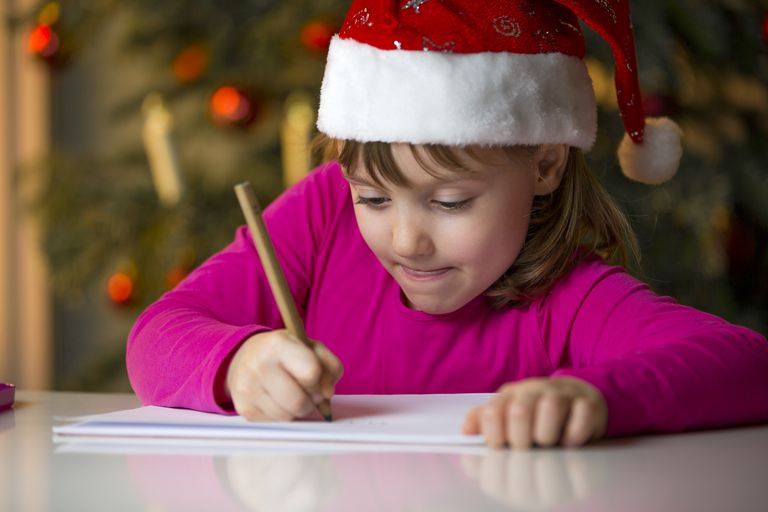 Little girl with Christmas cap writing a Christmas list