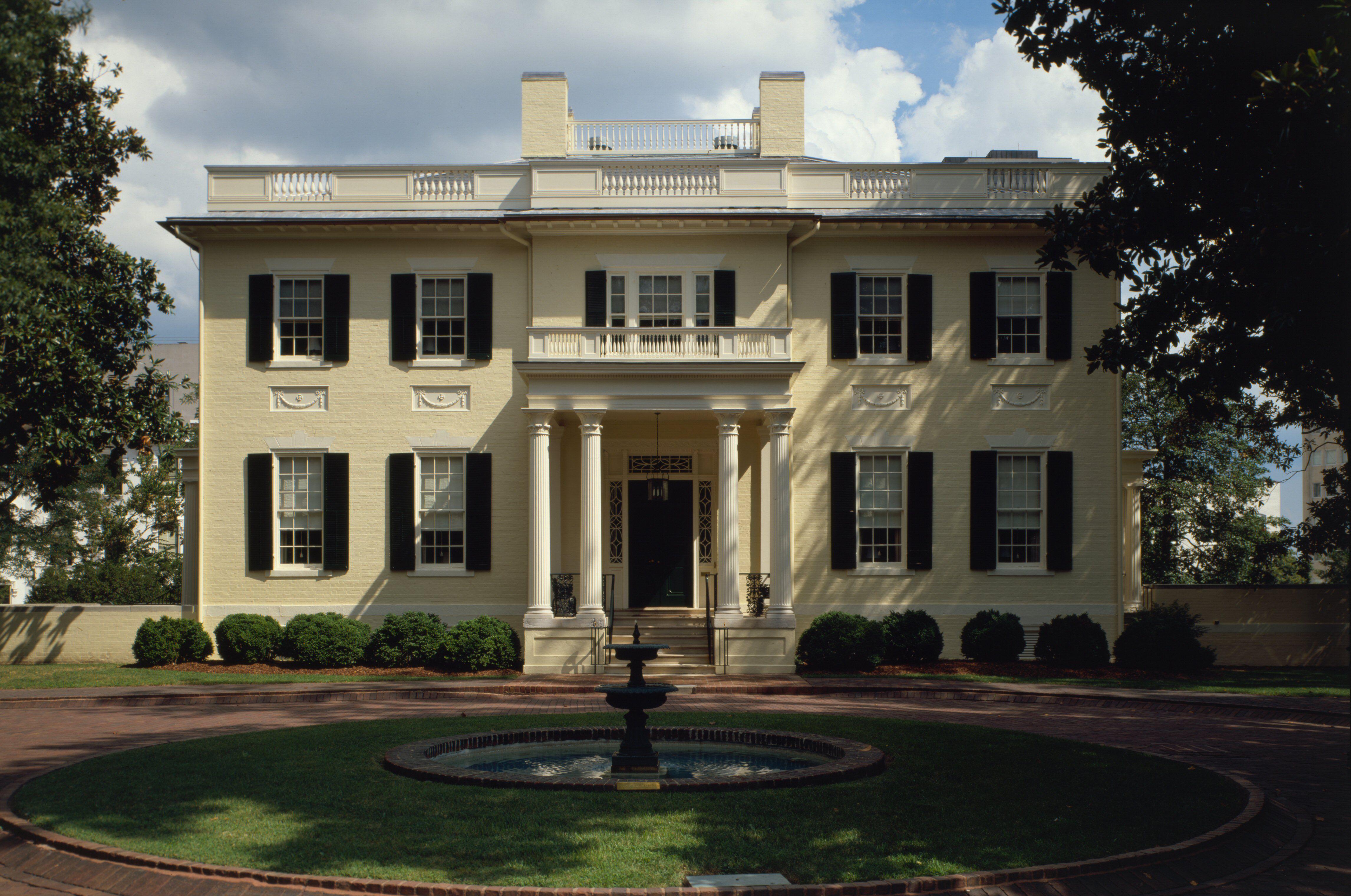maçonnerie jaune maison à deux étages avec des volets noir, petit portique à colonnes, le toit plat avec garde-corps le long du bord, fontaine hardscape au premier plan