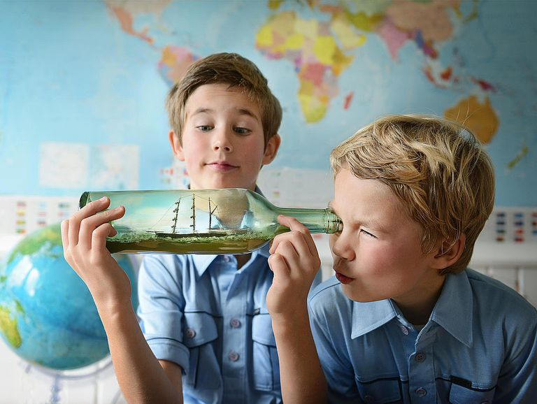 Boys playing with a ship in a bottle