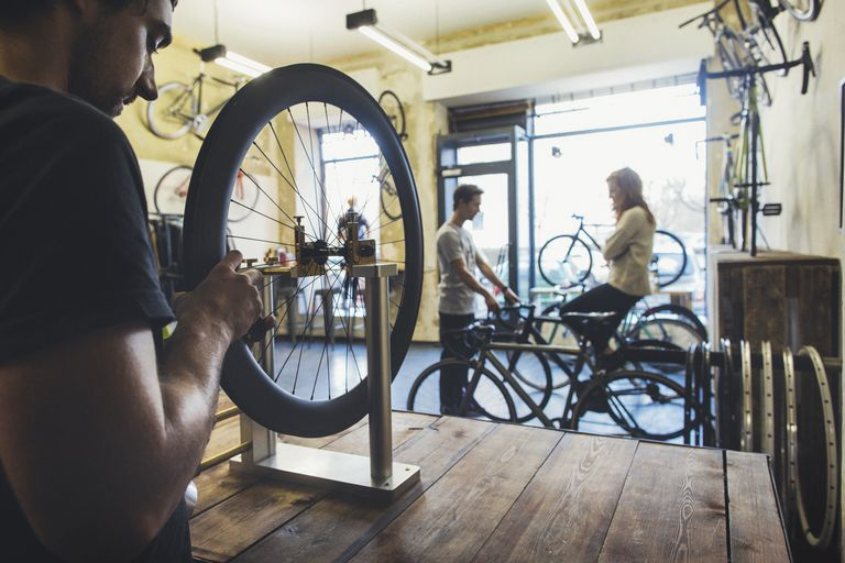 Mechanic, salesman and client in a custom-made bicycle store
