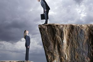 Woman looking up a cliff at a man