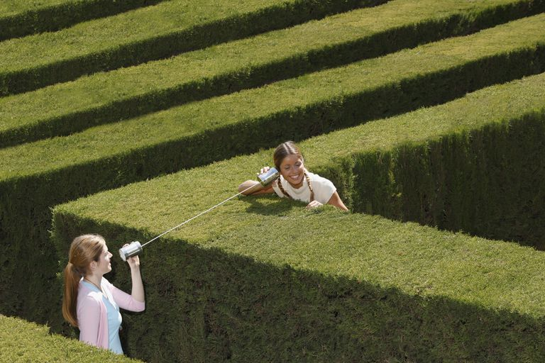 Two girls using a tin can telephone in a hedge maze