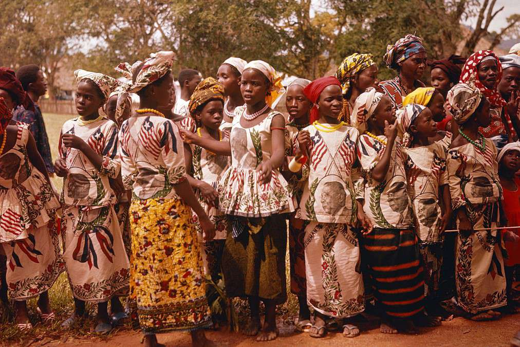 Girls wear dresses depicting the Liberian flag and political leaders during the national commemoration.