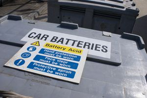 Battery acid caution sign on a plastic container.
