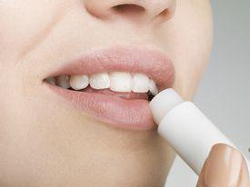 Woman applying lip balm, close up