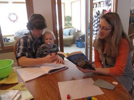 Mother, son, and toddler during a homeschooling lesson.