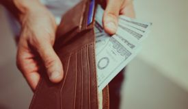 Man taking money out of wallet close up view.