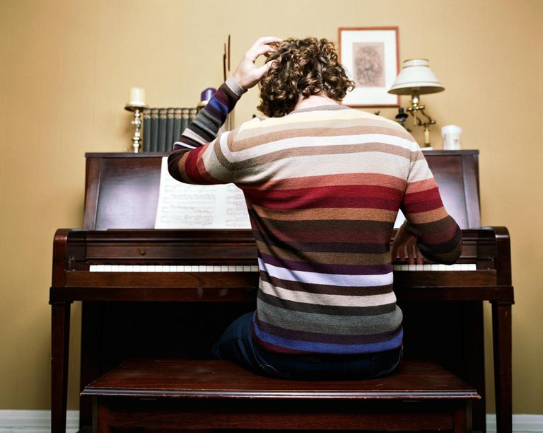 Young man practicing piano, rear view