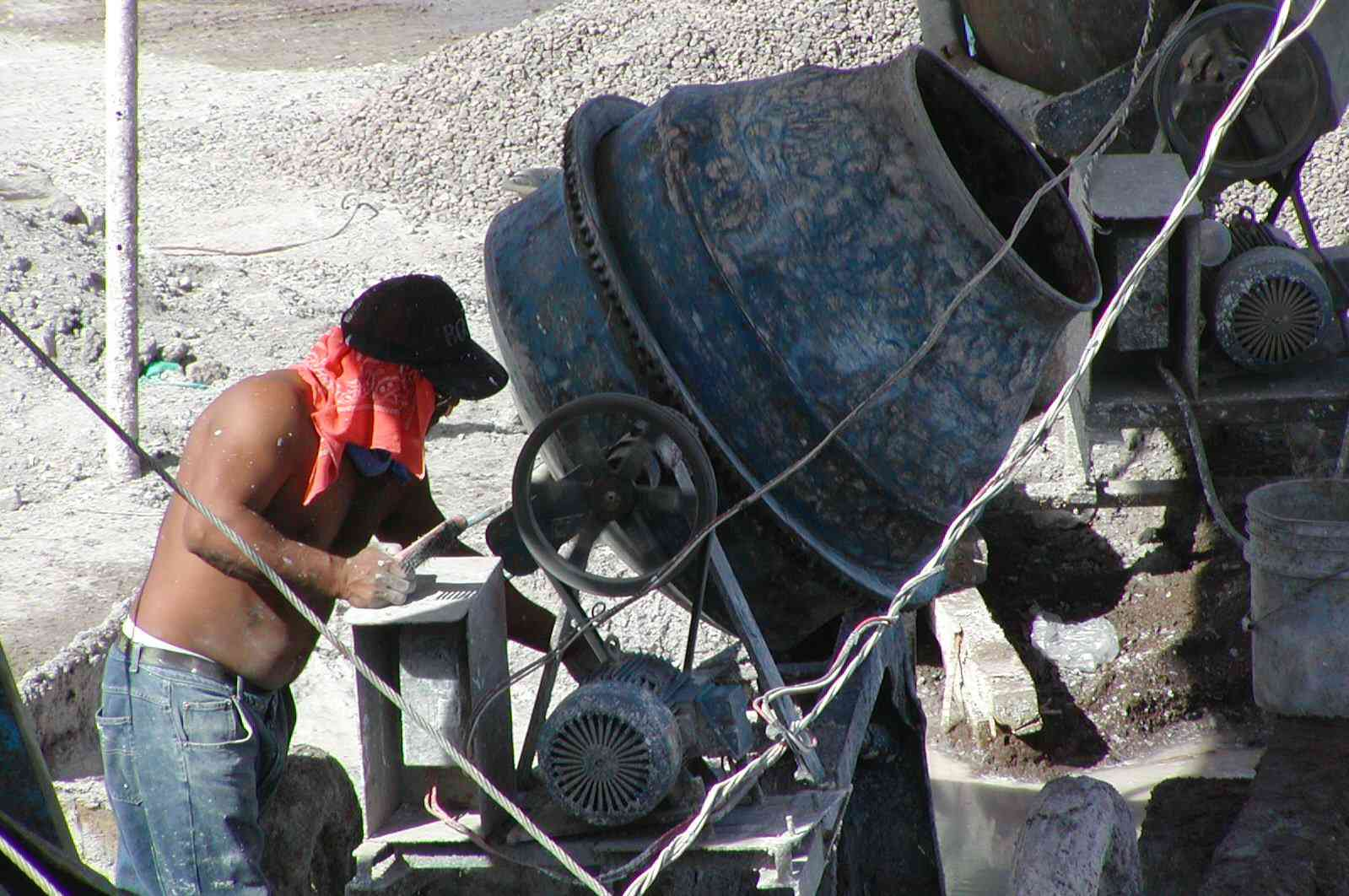 man in jeans without shirt, red scarf under hat, works a small, round, cement-mixer-type machine