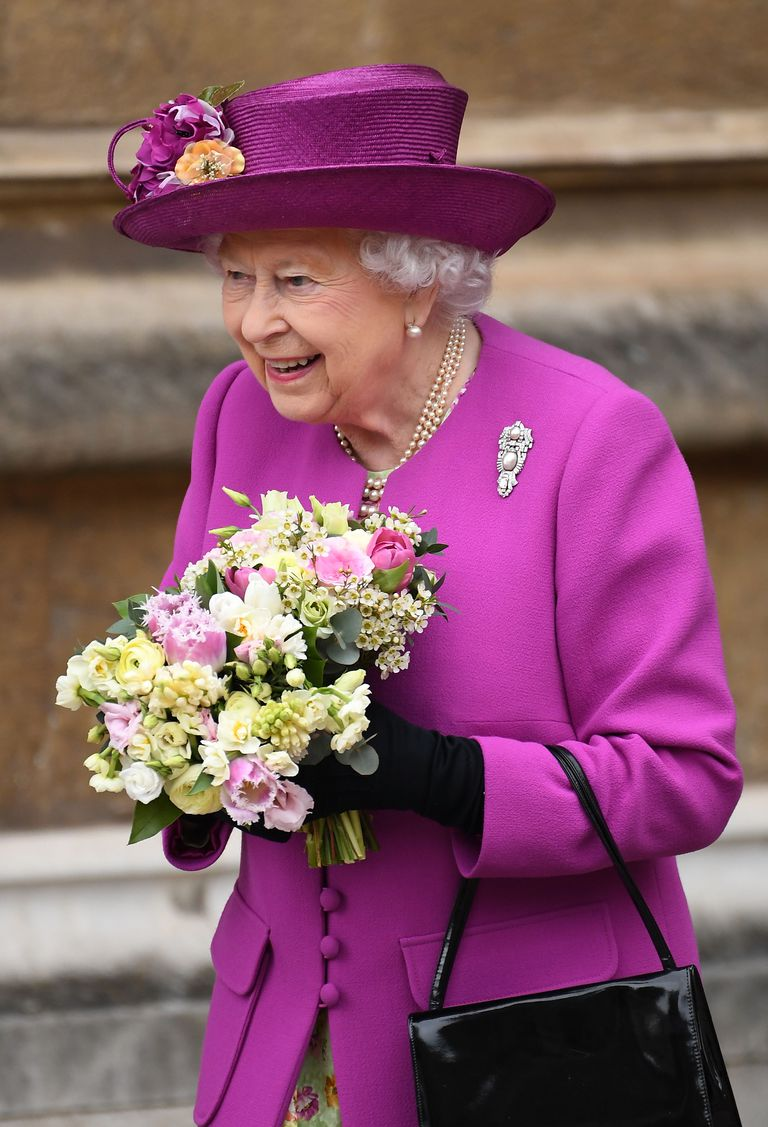 Queen Elizabeth II in purple holding a bouquet.
