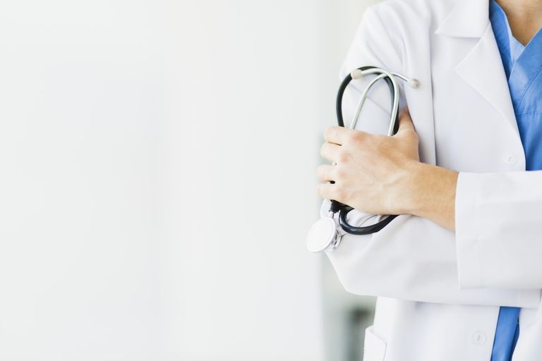 Doctor holding a stethoscope standing before a white background.