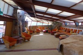 mid-century modern room, slanted ceiling, natural light, stone fireplace, built-in row of seating