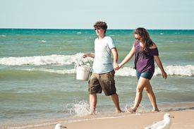 Young man and woman walking on beach