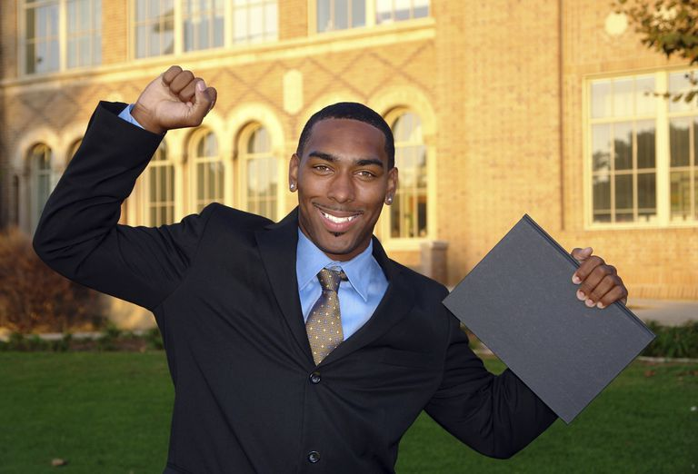 young man in a suit celebrating in front of a college building