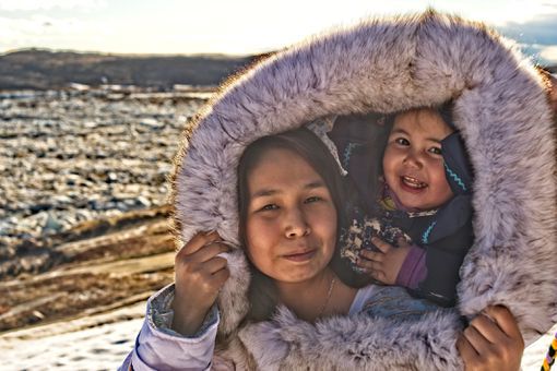 Inuit mother and daughter on Baffin Island, Nunavut, Canada, in traditional dress out on the tundra.
