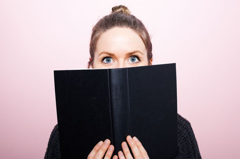 Young woman looking over the top of a book