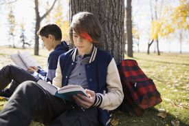Tween boys reading books leaning on tree trunk in autumn park