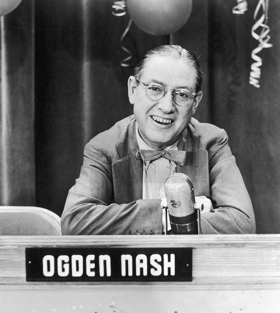 Ogden Nash, wearing eyeglasses and a bow tie, smiles while sitting on TV quiz show panel