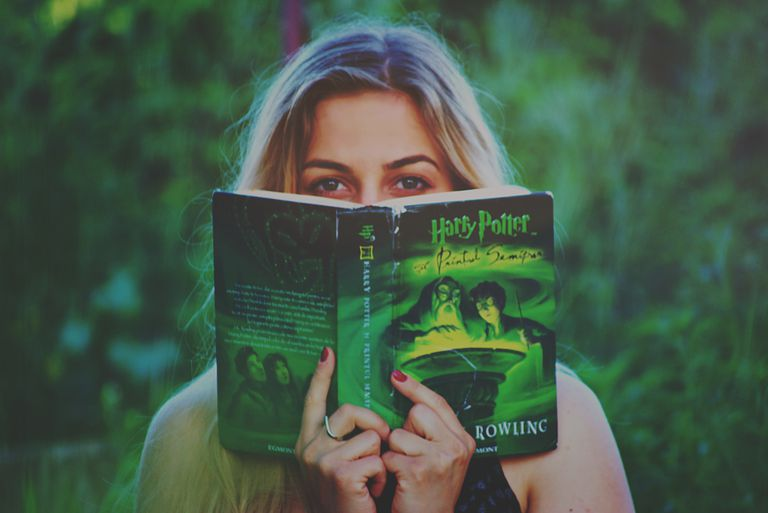 Woman reading a Harry Potter book.