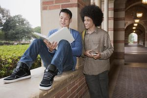 Mixed race student looking at notebook with friend