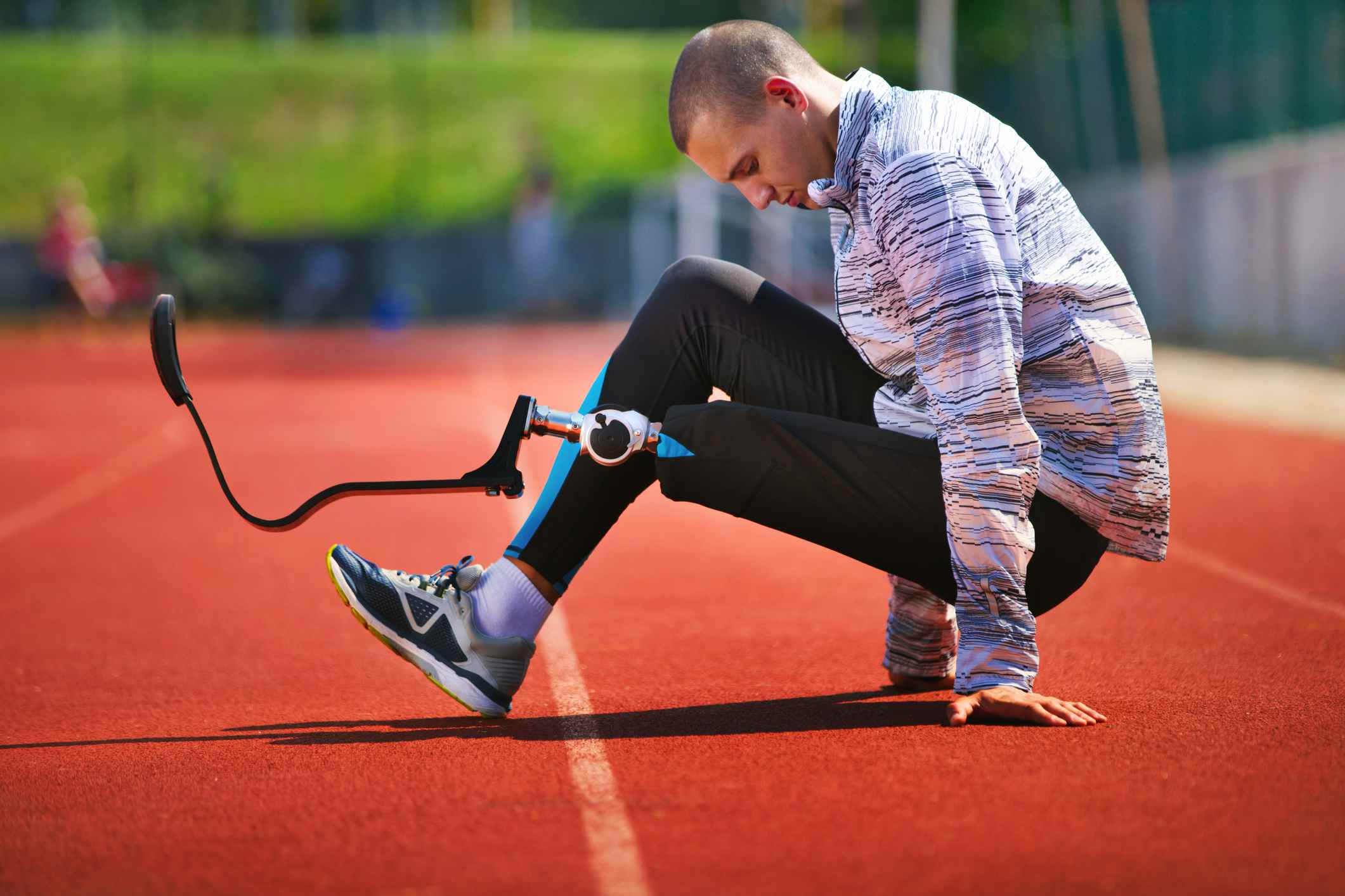 Young man with carbon fiber prosthetic limb exercising on a sunny day at a track