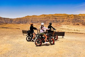 Three people on bikes in a desert landscape under a bright blue sky.