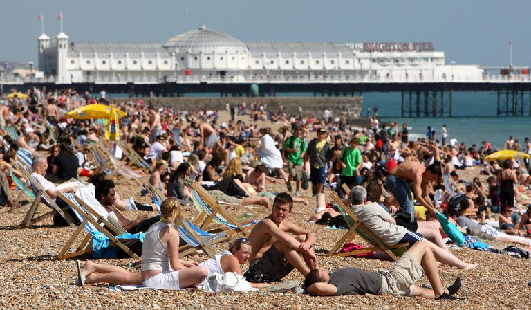 Large crowd sitting on beach next to pier.