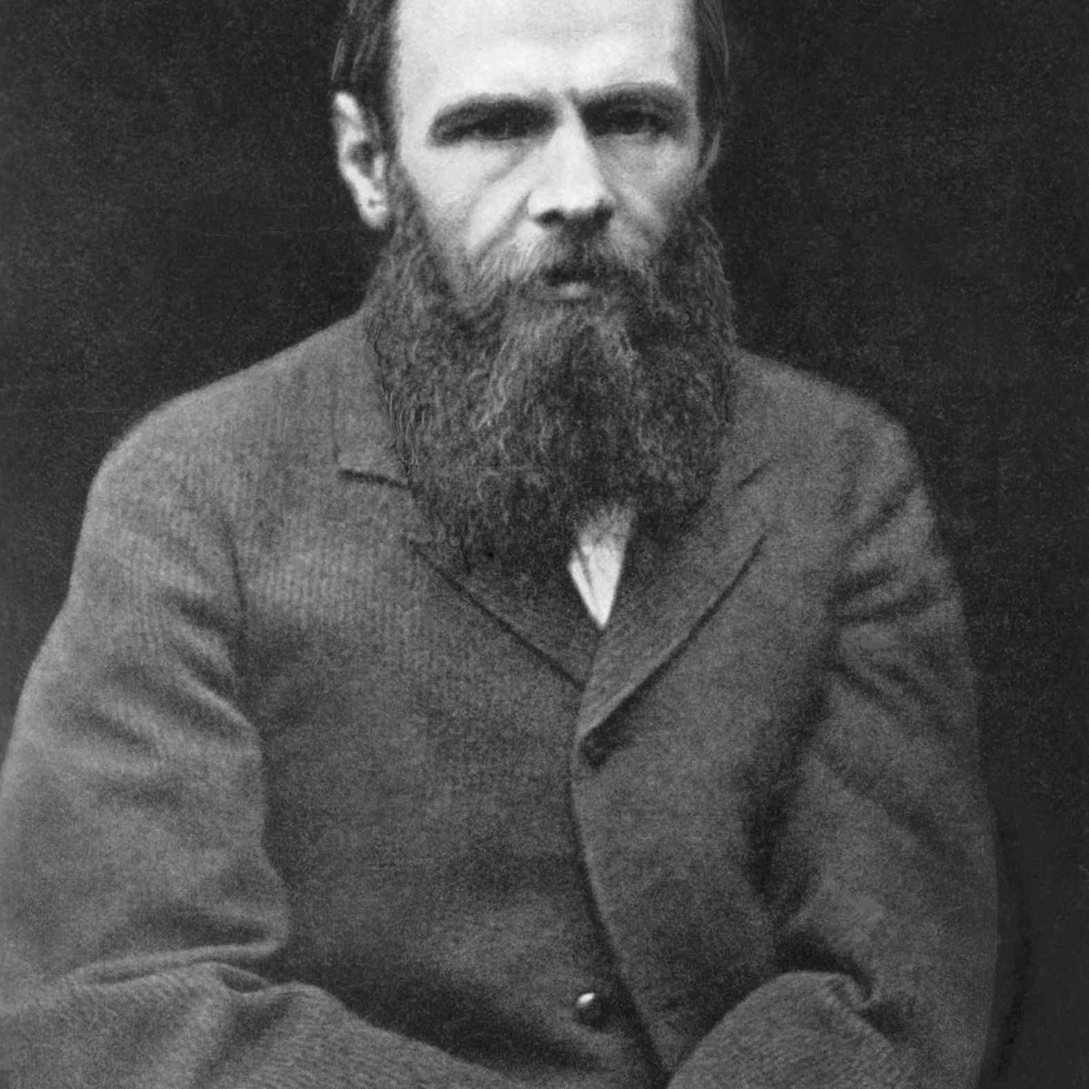 Black and white photograph of Dostoevsky, bearded and wearing a coat
