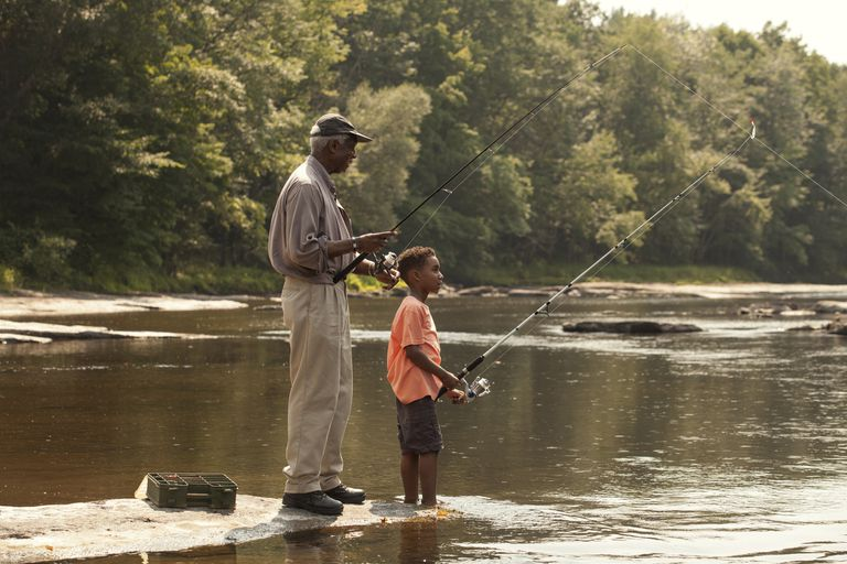 Grandfather and grandson fishing in lake