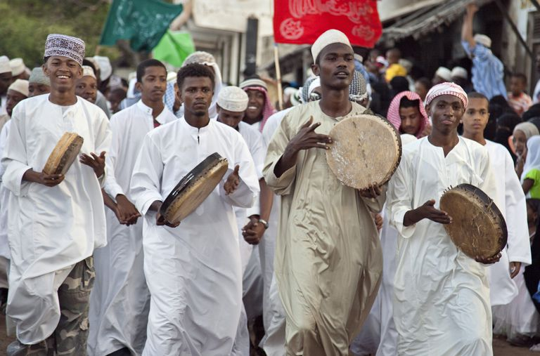 Kenya. A procession of the faithful singing and dancing through Lamu s narrow streets during the procession for Maulidi.